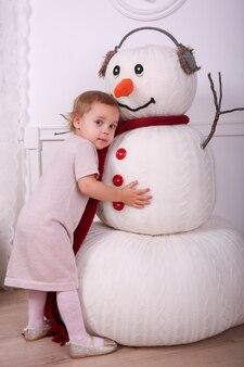Adorável menina abraça um boneco de neve grande engraçado