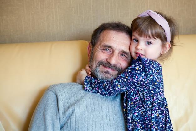 Adorável menina abraçando seu avô barbudo