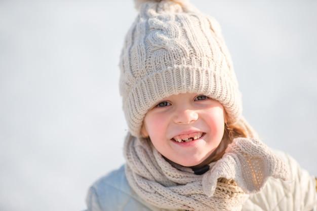 Adorável menina andando de skate no dia de neve de inverno ao ar livre