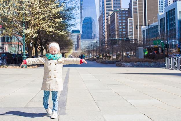 Adorável menina andando na cidade de nova york em dia ensolarado de primavera