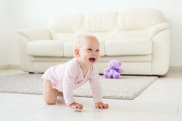 Adorável menina aprendendo a engatinhar na sala branca e ensolarada.