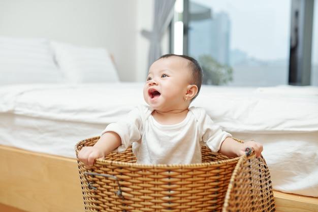 Adorável menina asiática brincando no cesto de roupa suja de vime no quarto