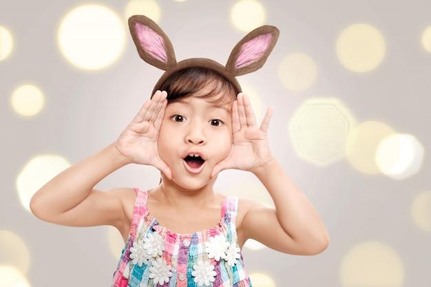 Adorável menina asiática com orelhas de coelho no feriado de páscoa