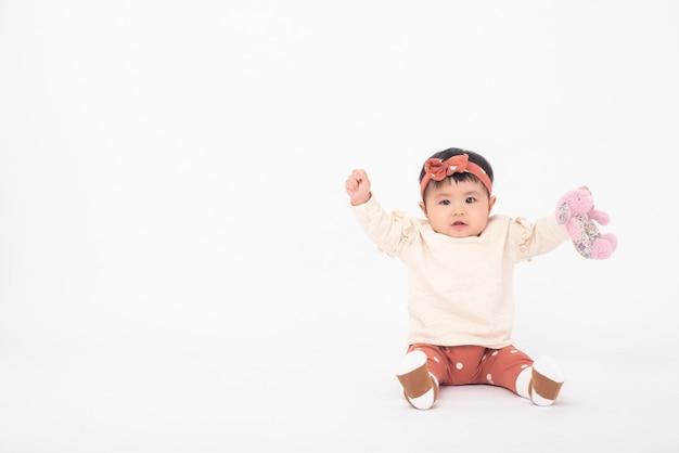 Adorável menina asiática é retrato na parede branca