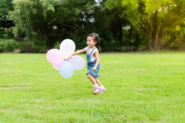 Adorável menina asiática está correndo e segurando o balão multicolor no parque