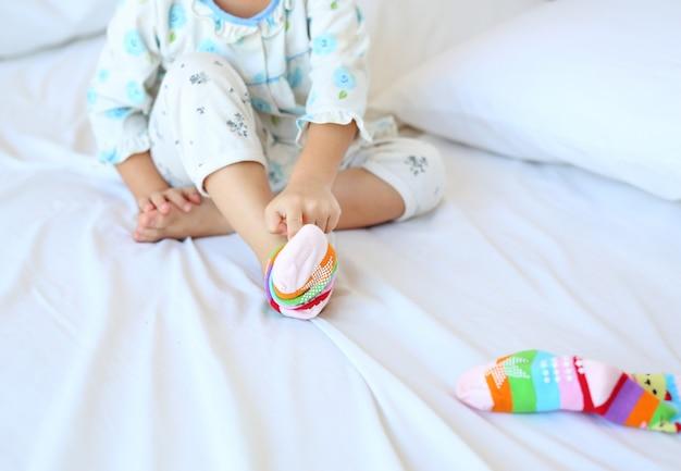 Adorável menina asiática tentando colocar as meias na cama.