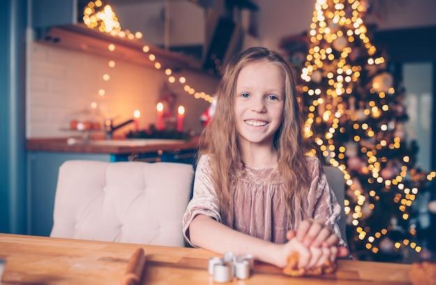 Adorável menina assando biscoitos de gengibre de natal