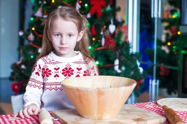 Adorável menina assar biscoitos de gengibre para o natal na cozinha