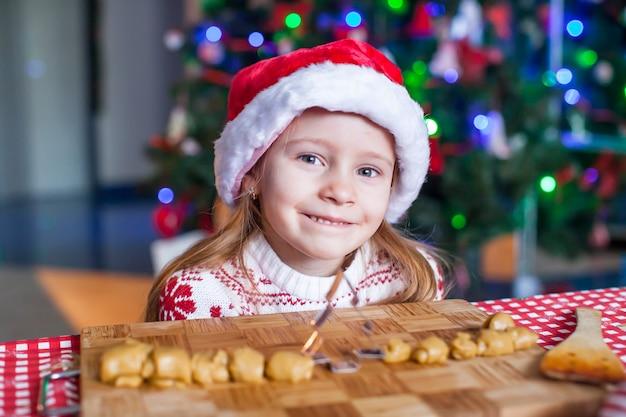 Adorável menina assar biscoitos de gengibre para o natal