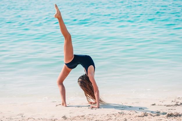 Adorável menina ativa na praia durante as férias de verão
