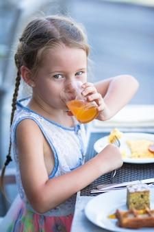 Adorável menina bebendo suco de maçã no café da manhã no café ao ar livre