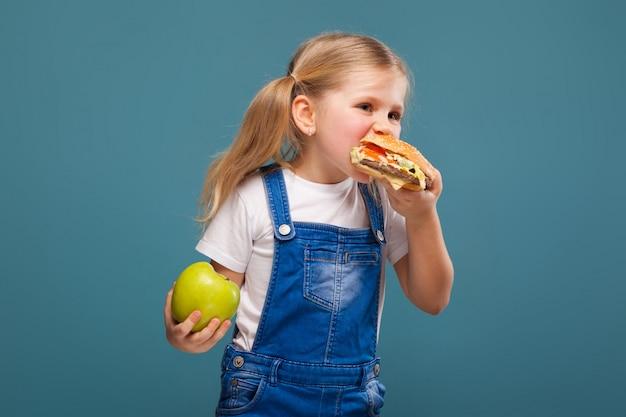 Adorável menina bonitinha em camisa branca e macacão jeans com hambúrguer e maçã