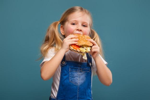 Adorável menina bonitinha em camisa branca e macacão jeans com hambúrguer