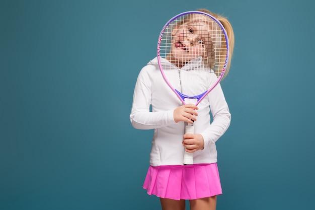 Adorável menina bonitinha na camisa branca, jaqueta branca e saia rosa com raquete de tênis