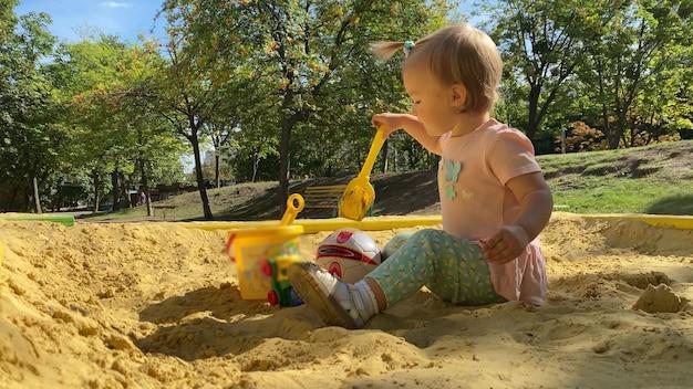 Adorável menina brinca na caixa de areia com brinquedos.