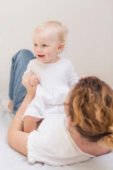 Adorável menina brincando com a mãe