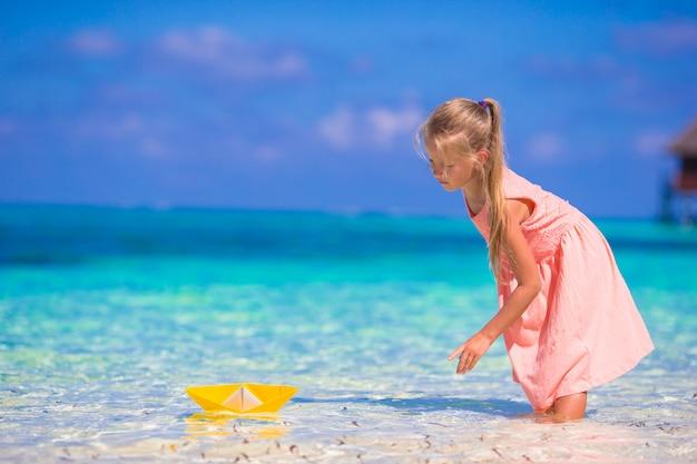 Adorável menina brincando com barco de origami no mar azul-turquesa