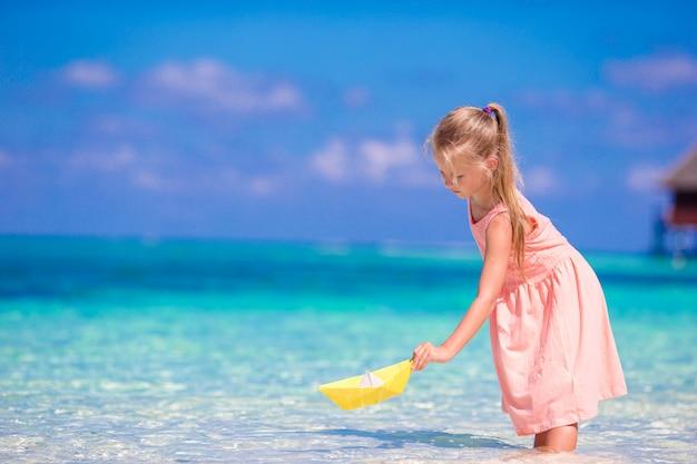 Adorável menina brincando com barco de origami no mar turquesa