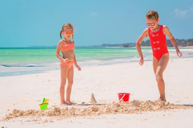 Adorável menina brincando com brinquedos de praia na praia tropical branca