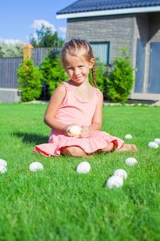 Adorável menina brincando com ovos de páscoa brancos no quintal