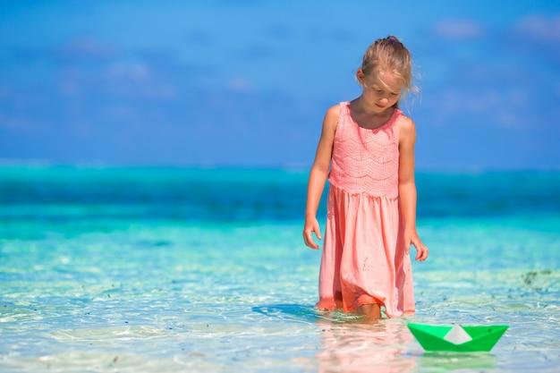 Adorável menina brincando com papel barco no mar azul-turquesa