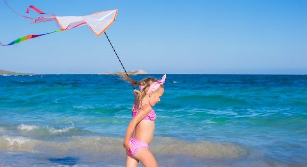 Adorável menina brincando com pipa na praia tropical