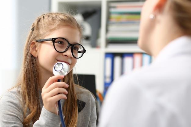 Adorável menina brincando de médico com estetoscópio na clínica