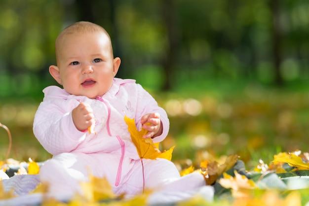 Adorável menina brincando em um parque no outono, sentada no chão entre coloridas folhas amarelas com espaço de cópia