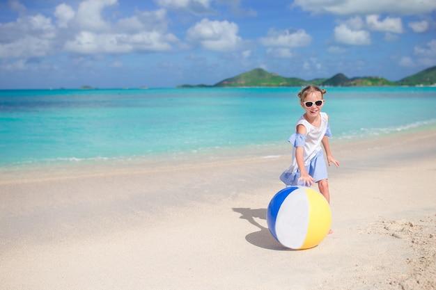 Adorável menina brincando na praia com bola