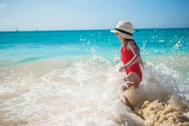 Adorável menina brincar com água na praia durante as férias do caribe