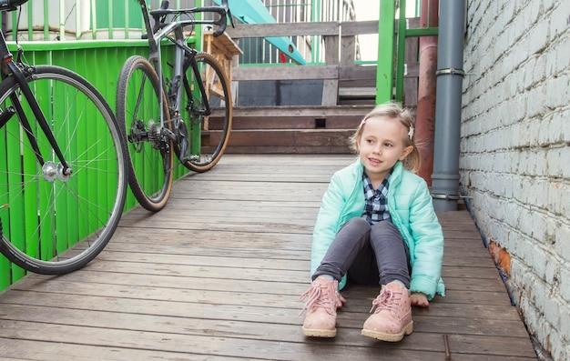 Adorável menina caucasiana sentada em um deck de madeira ao lado de uma parede de tijolos, olhando para a câmera