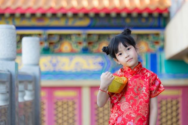 Adorável menina chinesa feliz recebendo barra de ouro no ano novo chinês