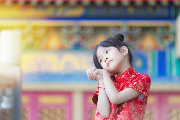 Adorável menina chinesa feliz sonhando com presente de envelope de seus pais para o ano novo chinês abençoe