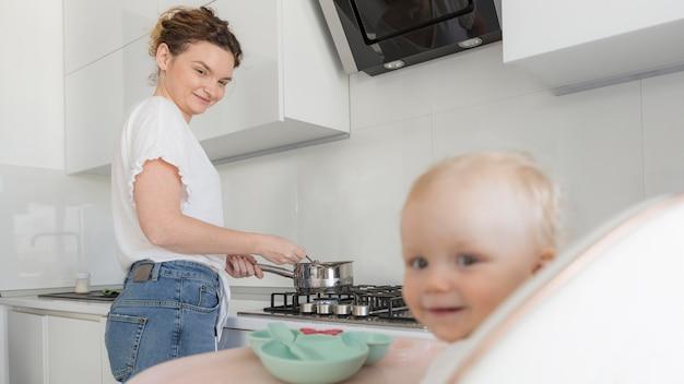 Adorável menina com a mãe na cozinha