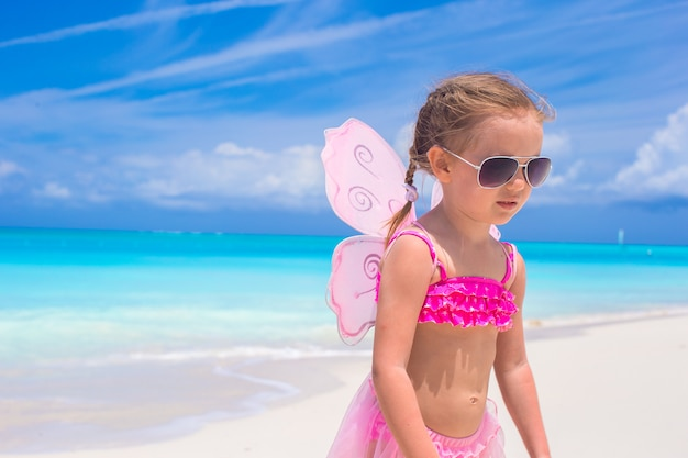 Adorável menina com asas como borboleta em férias na praia