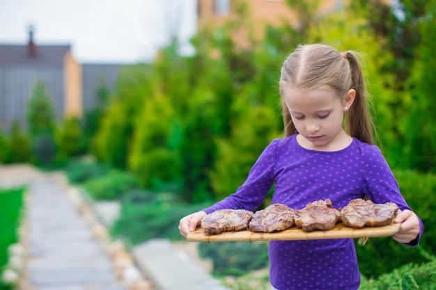 Adorável menina com bifes grelhados nas mãos ao ar livre