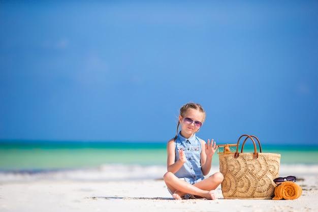 Adorável menina com bolsa de praia e toalha durante as férias de verão