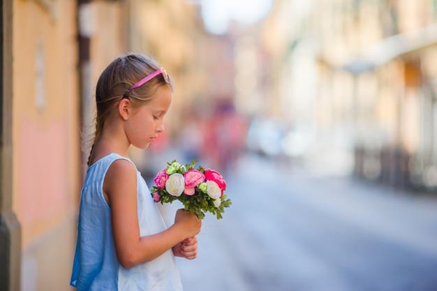 Adorável menina com buquê de flores andando na cidade europeia