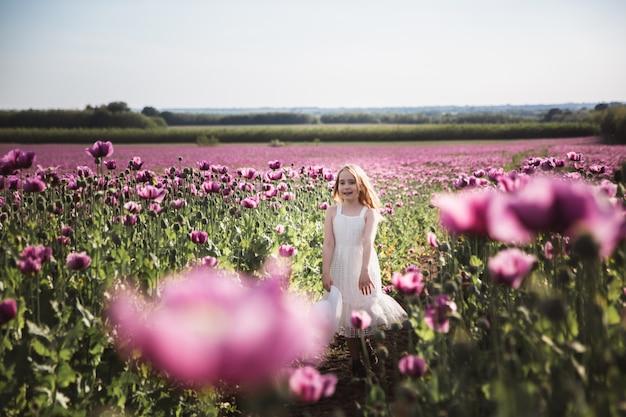 Adorável menina com cabelo comprido vestido branco solitário andando no campo de flores lilás papoula