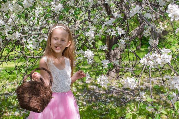 Adorável menina com cesto de palha no pomar de florescimento