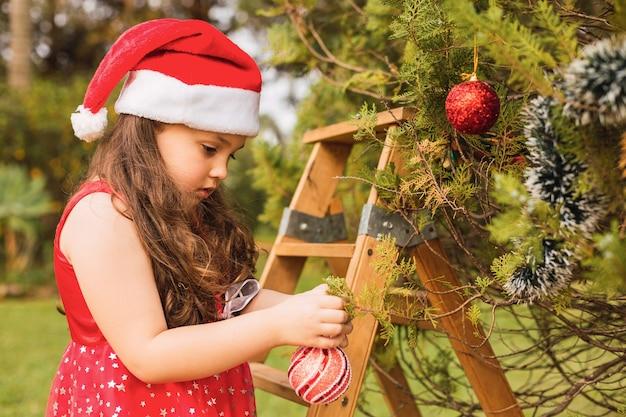 Adorável menina com chapéu de natal decorando a árvore de natal ao ar livre