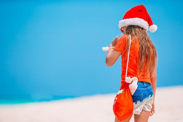 Adorável menina com chapéu de papai noel com uma sacola de presentes em uma praia tropical