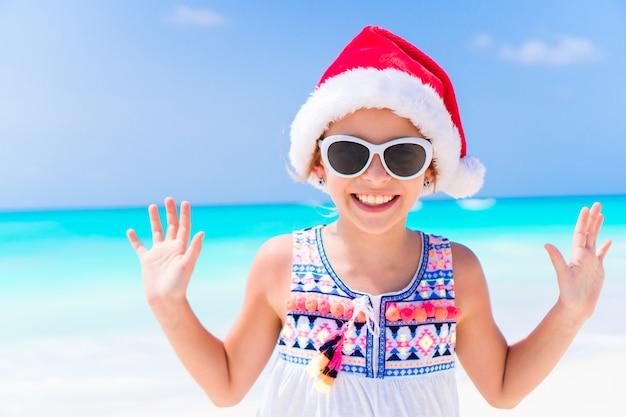 Adorável menina com chapéu de papai noel durante as férias de praia de natal
