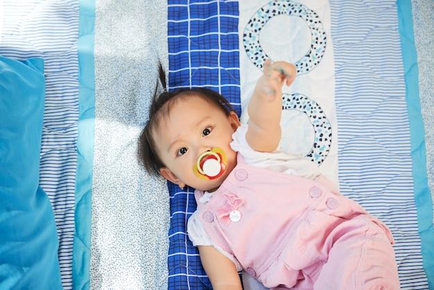 Adorável menina com chupeta na boca, deitada na cama e apontando para a câmera com o dedo indicador