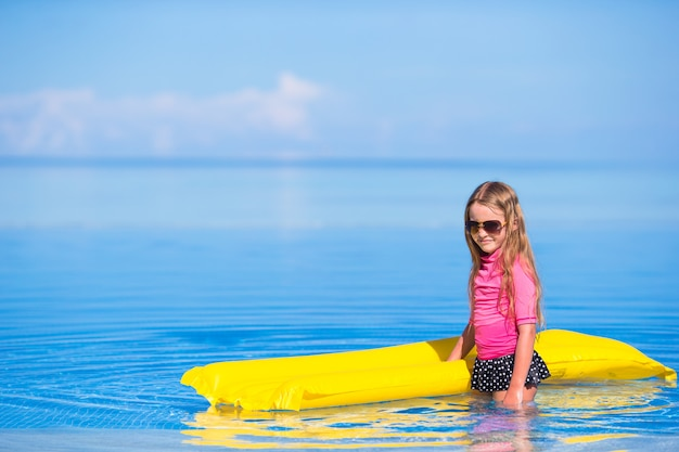 Adorável menina com colchão inflável na piscina ao ar livre