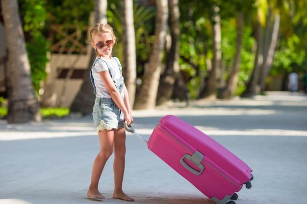 Adorável menina com grande bagagem durante as férias de verão