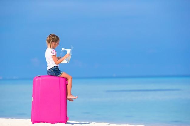Adorável menina com grande bagagem e mapa da ilha na praia branca