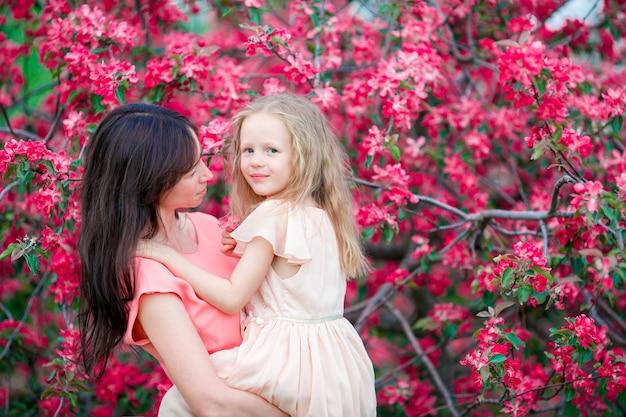 Adorável menina com jovem mãe em cerejeira desabrochando jardim na primavera