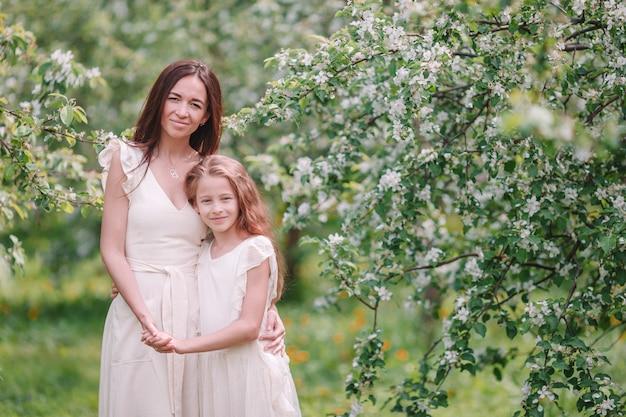 Adorável menina com jovem mãe no jardim de cerejeira desabrocham no lindo dia de primavera