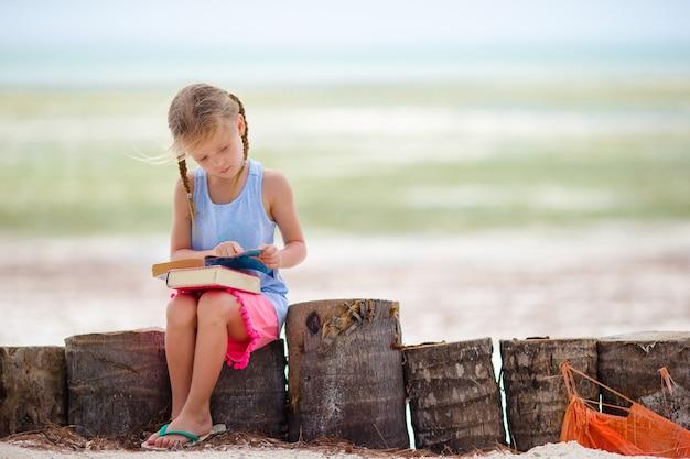 Adorável menina com livro na praia tropical branca